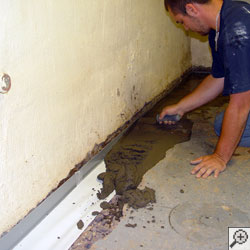 A contractor installing fresh concrete over a French drain tile installation in a basement
