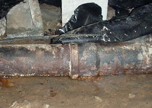 A damaged sewage line in a crawl space