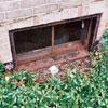Heavily rusting basement windows, almost falling apart.