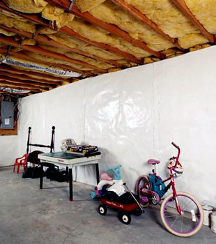 A concrete basement wall with our vapor barrier system installed on its surface