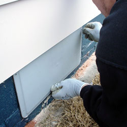 Installation of a plastic crawl space vent cover.