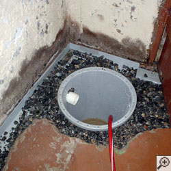 a sump pump system being installed in the corner of a basement, with clean stone and durable plastic liner.