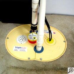 A TripleSafe battery backup sump pump system installed on a basement floor.