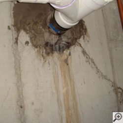 A leaking pipe penetration point in a basement wall.