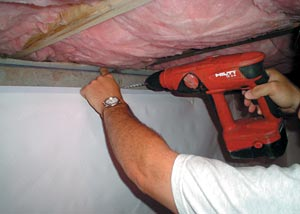 A contractor sealing a block wall foundation in a crawl space