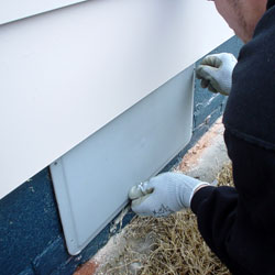 A contractor sealing a crawl space vent