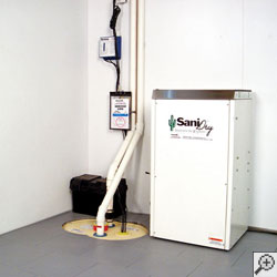 Our basement dehumidifier system installed in a waterproofed basement with walls and flooring installed.