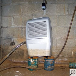 A dehumidifier sitting on two coffee cans, with a mud stain a third of the way up the system from floodwaters.