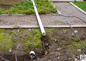 a drainage pipe is buried and clogged, and a second drainage pipe is overheat and not buried, but is laid across a walkway where someone could trip on it.
