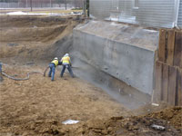 Applying shotcrete to bottom section of wall and to sand backfill above