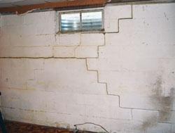 Mur de fondation à Montréal avec des fissures et flambage vu a l'intérieur du sous-sol