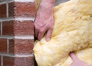 Isolant en fibre de verre installé dans un sous-sol avec des murs de brique.