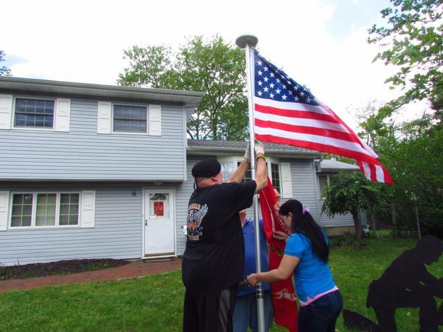 Veteran Fred begins to add his flag to the American Flag Pole