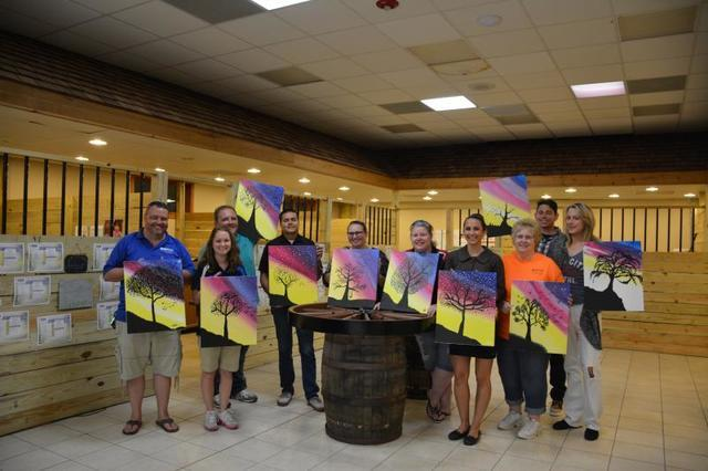 Team DryZone with the paintings from the fundraiser.