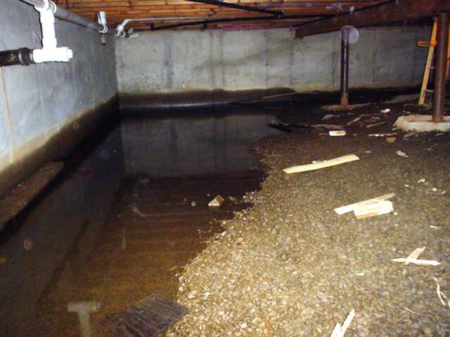 A crawl space with a large puddle of water on the gravel floor