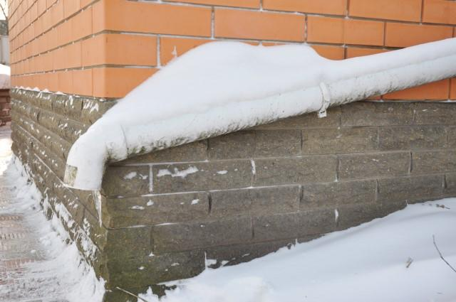 A frozen downspout and snow piled near a home