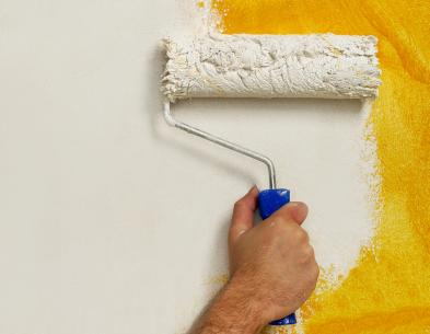 Painting wall white with paint roller.