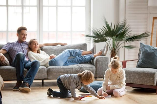 Family relaxing and kids playing in a living room