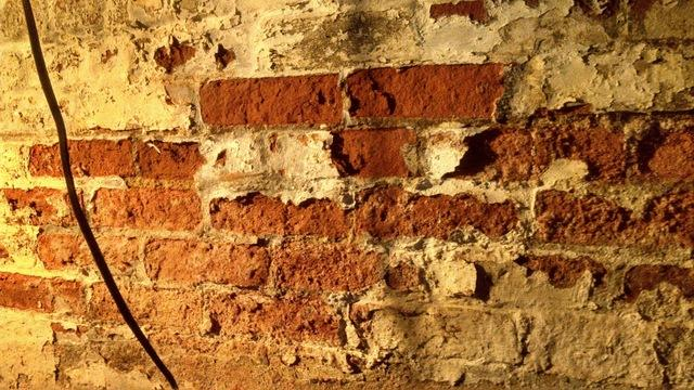 Water in this brick basement wall is causing the paint to peel off, and the brick to crumble.