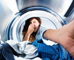 lady pinching her nose as she takes laundry out of washer