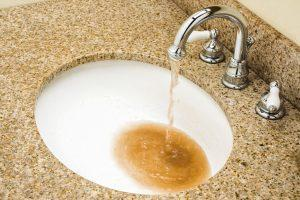 sink with brown water coming out of it