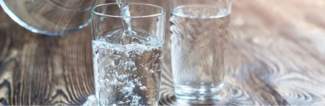Two glasses of clear water on a table