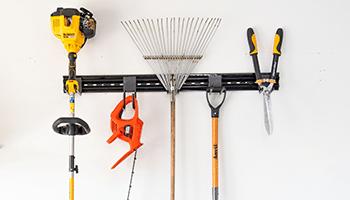 yard tools organized on a garage track system
