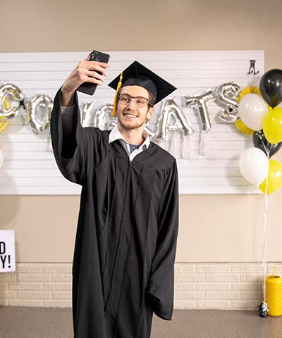 New graduate taking a selfie in front of a graduation party photo backdrop.