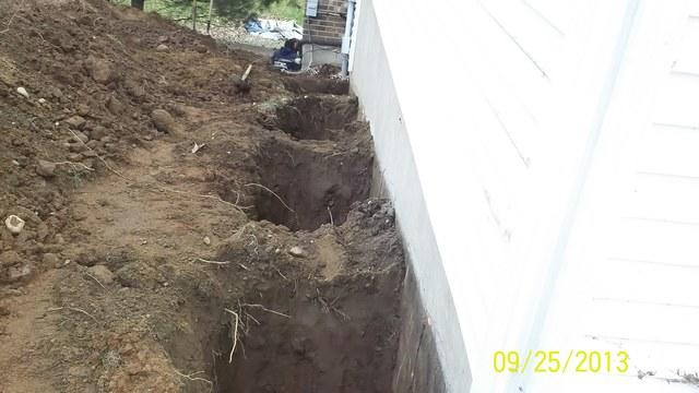 Foundation repair at a colonial with an attached garage and an addition in ...