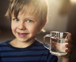 Young boy holding a glass of water