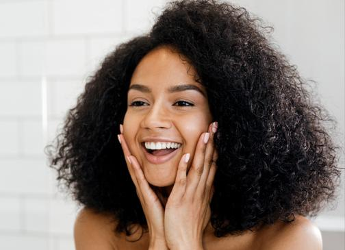 woman looking in mirror happy with skin and hair