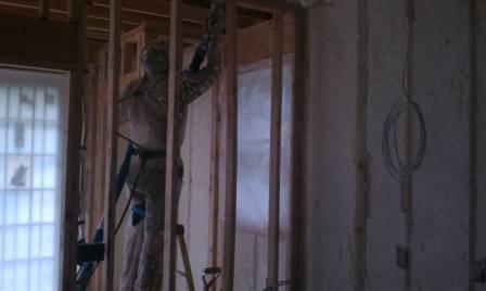 Alex installing spray foam to a wall