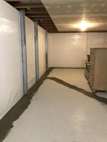 This photo displays another wall with the PowerBrace system, in addition to the waterproofing installed throughout the basement.