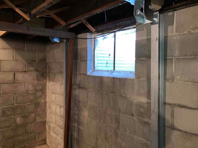 The PowerBrace beams run from top to bottom and can be tightened over time to return the wall to its vertical position.