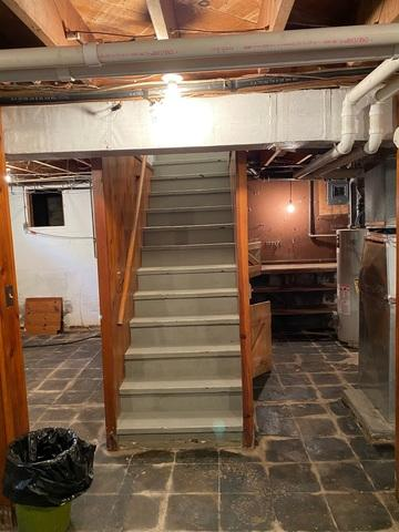 The staircase to the basement shows the impact of water damage on the floors and the wood.