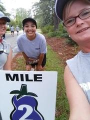 Marketing Manager Kimberly Mobley takes a picture with Administrative Assistant Josseline Gonzalez and Accounting Manager Lacie Holden at the 2 mile marker.
