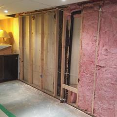 A view of the previously finished area of the basement where seepage from the wall and footing caused damage to the insulation and drywall.