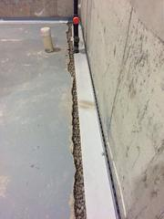 A view inside the basement where the concrete has been jack hammered and removed to allow room for the new WaterGuard® drainage system to be installed. It is now ready to be cemented in place.