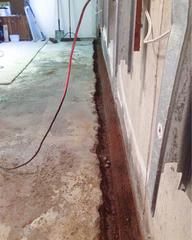 Inside the basement of the exposed and cleaned footing where the WaterGuard® drain system will be installed.