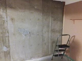 A view of the problematic basement wall. Notice the honeycombing of the concrete, which is the cause of the water issues in this home.