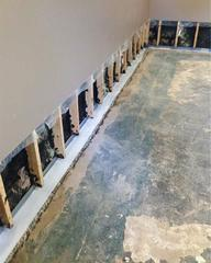 A view of the basement during the installation of the WaterGuard® system on the footing of the home, ready to be cemented in place.