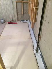 This is a section of the basement with WaterGuard® being installed on the foundation footing.