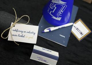 Some of the things that were on the table prior to the #1 team arrival for REDEFINE including name table cards, a new t-shirt, our Redefine Manifesto, a sticker, and a pen.