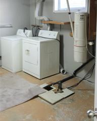 A view inside the laundry room in the basement where showing the existing sump pump system.