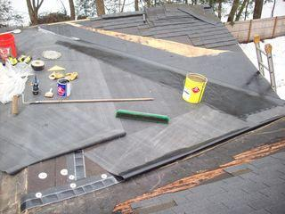 We see this project in progress, as the existing roof has already been stripped off and the underlayments for the new roof have been installed. The rubber for the roof has been laid out and just needs to be installed and some of the shingles replaced as well.
