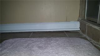 The rotten wood and subfloor had deteriorated, which caused it to sink away from the baseboard and wall.