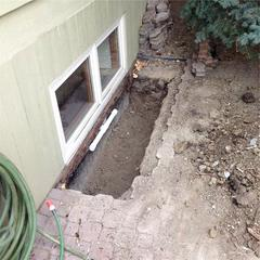 A view outside of the home after removing the old window well and installing the WellDuct® drain.