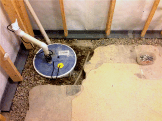 Within this photo you can see the CleanSpace® vapor barrier (the White material) installed against the wall leading down towards the WaterGuard® (the grey device). These devices work in tandem to direct any excess water to the newly installed SuperSump® Sump Pump System.