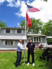Quality 1st owner, Tom Roman raises the flag for Vietnam Veteran, Fred Goger