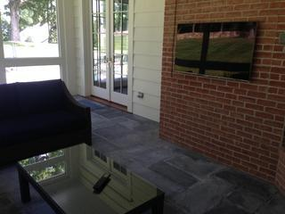 TV install on brick in enclosed sunroom with crestron remote.